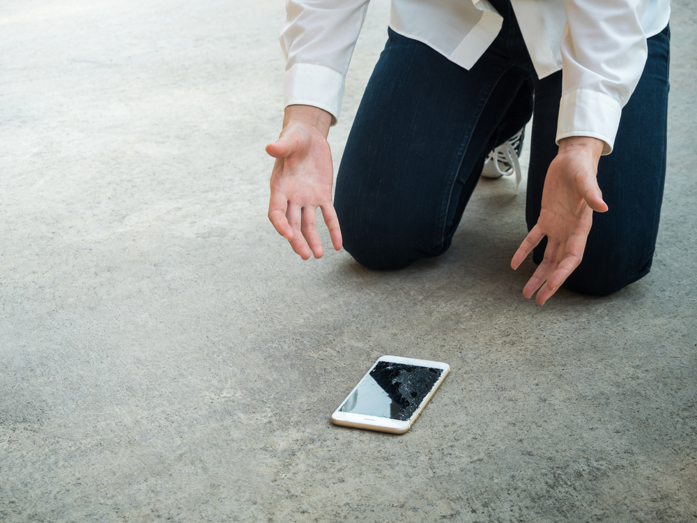 Mann kniet auf Teppich und begutachtet sein kaputtes Smartphone.