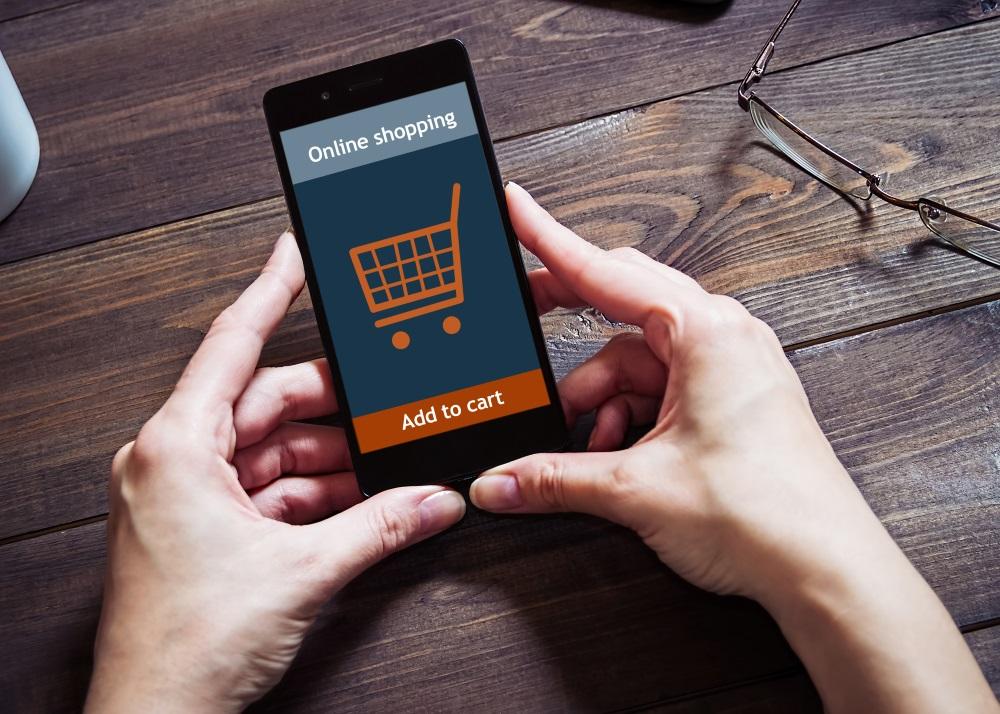 """Zwei Hände halten ein Smartphone, auf dem Display werden ein Einkaufswagen und die Worte """"Onlineshopping"""" und """"Add to Card"""" angezeigt."""
